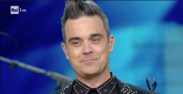 Robbie Williams che riflette sulle sue dubbie scelte di vita, pochissimi istanti dopo aver baciato la De Filippi